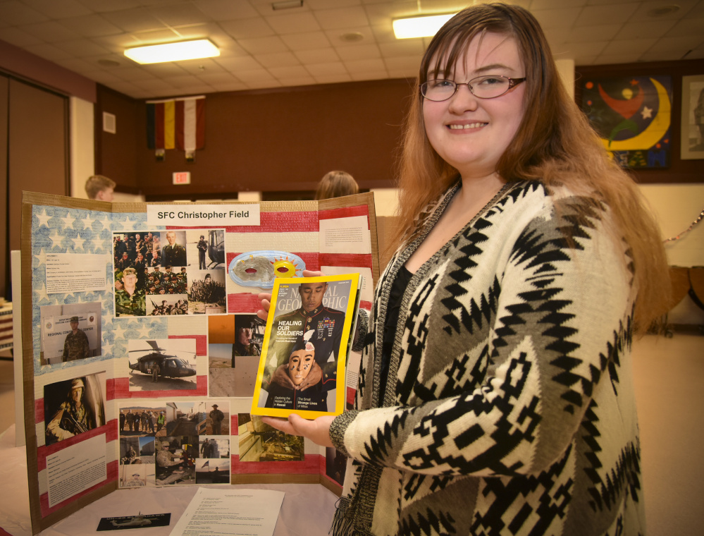 Monmouth Academy junior Sierra Cummings shows a copy of the National Geographic issue that inspired her social studies teacher, Jocelyn Gray, to create an art project on U.S. war veterans as a way to learn about living veterans and their war experiences. Cummings selected Sgt. First Class Christopher Field, of Durham, who currently works at Camp Keyes in Augusta, as the focus of her project. Cummings said she's known Field since she was little and thought that he'd be perfect for the project.
