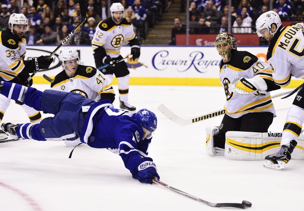 Maple Leafs right wing Connor Brown dives for the puck as Bruins defenseman Torey Krug (47), goalie Tuukka Rask and defenseman Adam McQuaid watch during the second period Monday night in Toronto. The Maples Leafs went on to a 4-2 win