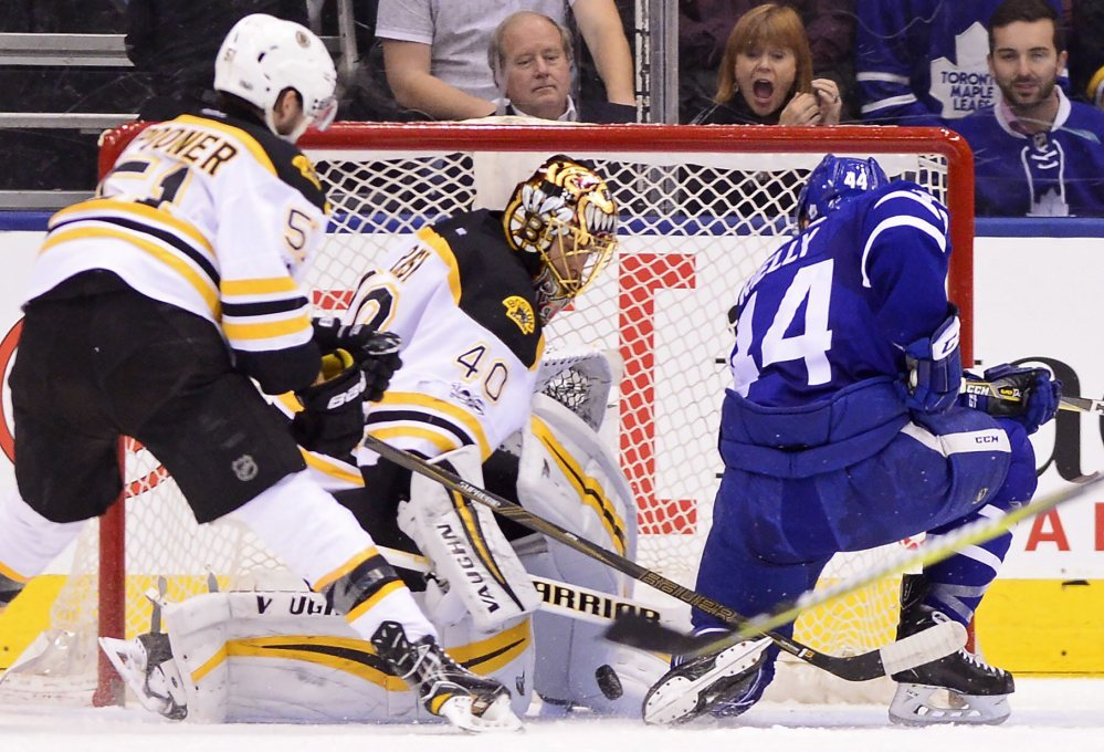 Maple Leafs defenseman Morgan Rielly scores on Tuukka Rask as Bruins center Ryan Spooner defends in the first period.