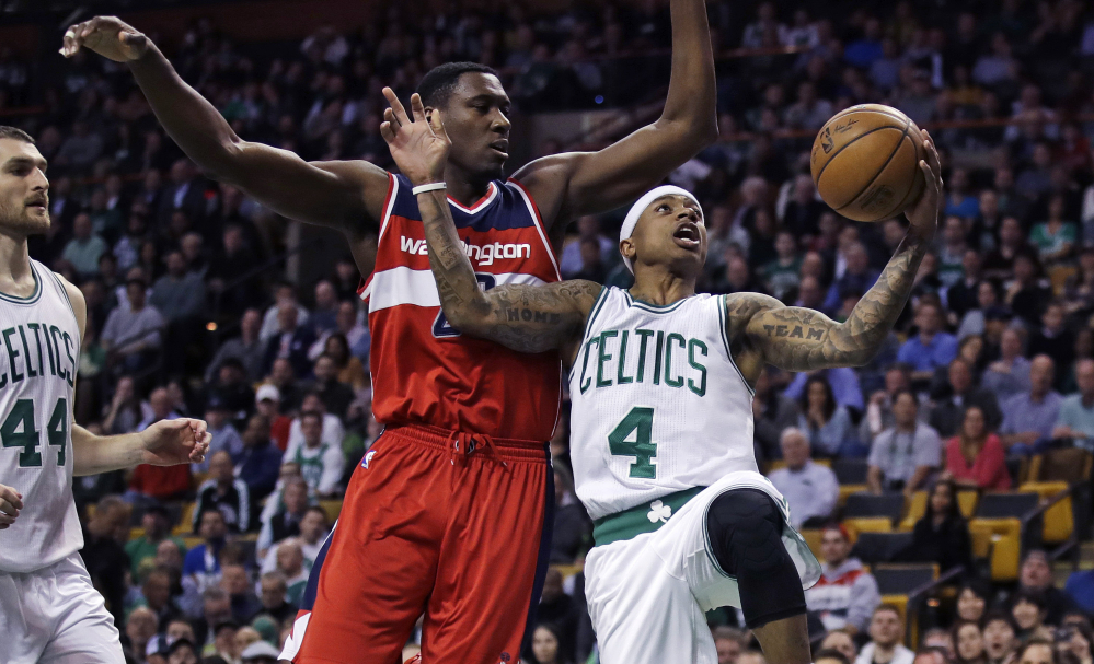 Boston's Isaiah Thomas, right, avoids the defense of Washington's Ian Mahinmi as he drives to the basket curing the Celtics' 110-102 win Monday at Boston. Thomas had 25 points in his return after missing two games with a knee injury.
