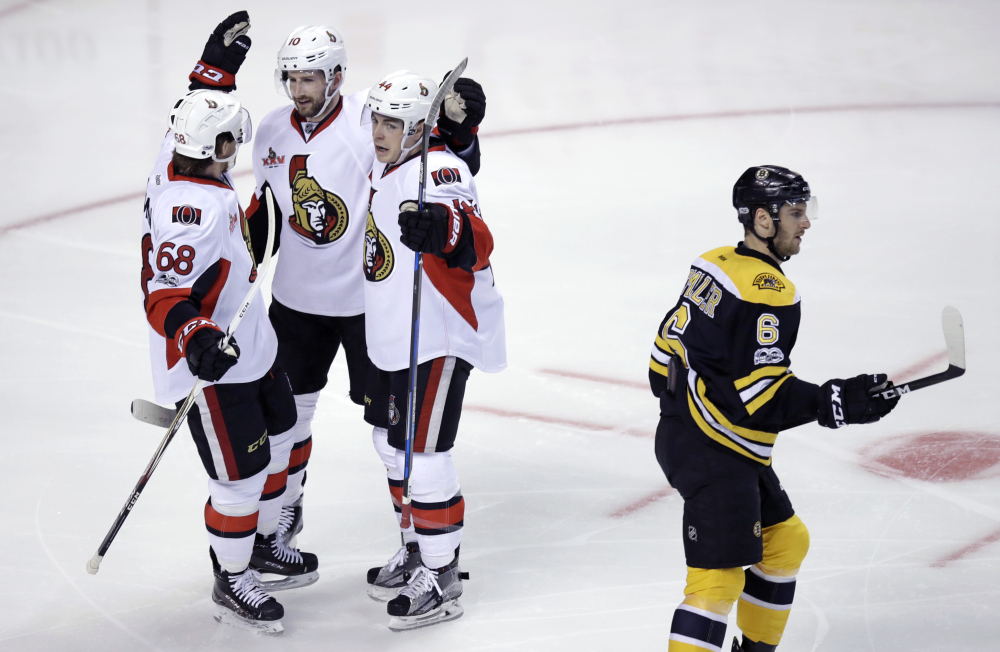 Ottawa Senators left wing Tom Pyatt, second from left, is congratulated by Mike Hoffman and Jean-Gabriel Pageau after his goal during the first period against the Boston Bruins. At right skating past is Bruins defenseman Colin Miller.