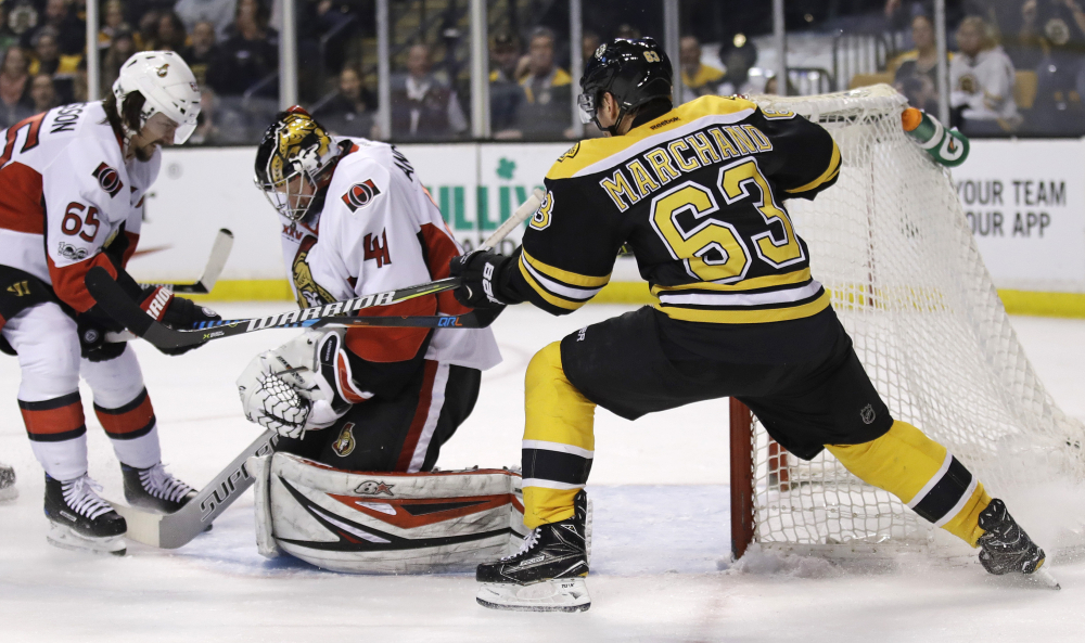 Boston Bruins left wing Brad Marchand tries to break the puck away from Ottawa Senators goalie Craig Anderson on a save during the second period Tuesday. At left is Ottawa Senators defenseman Erik Karlsson.