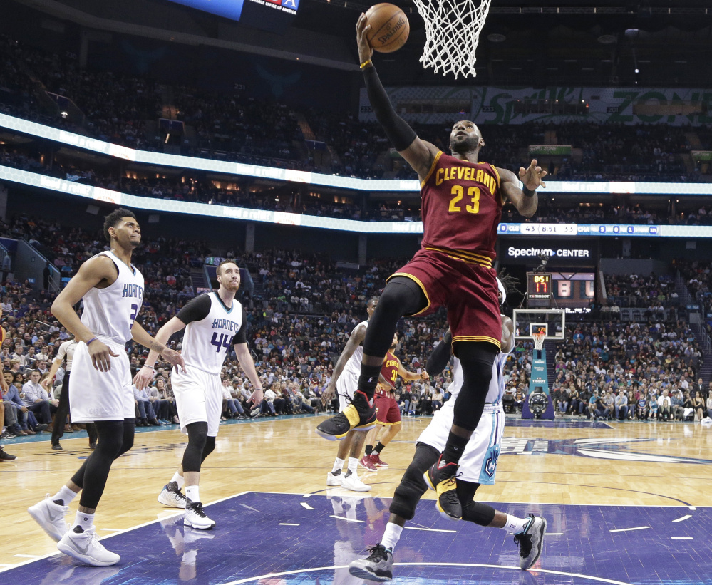 Cleveland's LeBron James drives to the basket during the Cavaliers' 112-105 win over Charlotte on Friday in Charlotte, N.C. James had 32 points, 11 assists and nine rebounds.