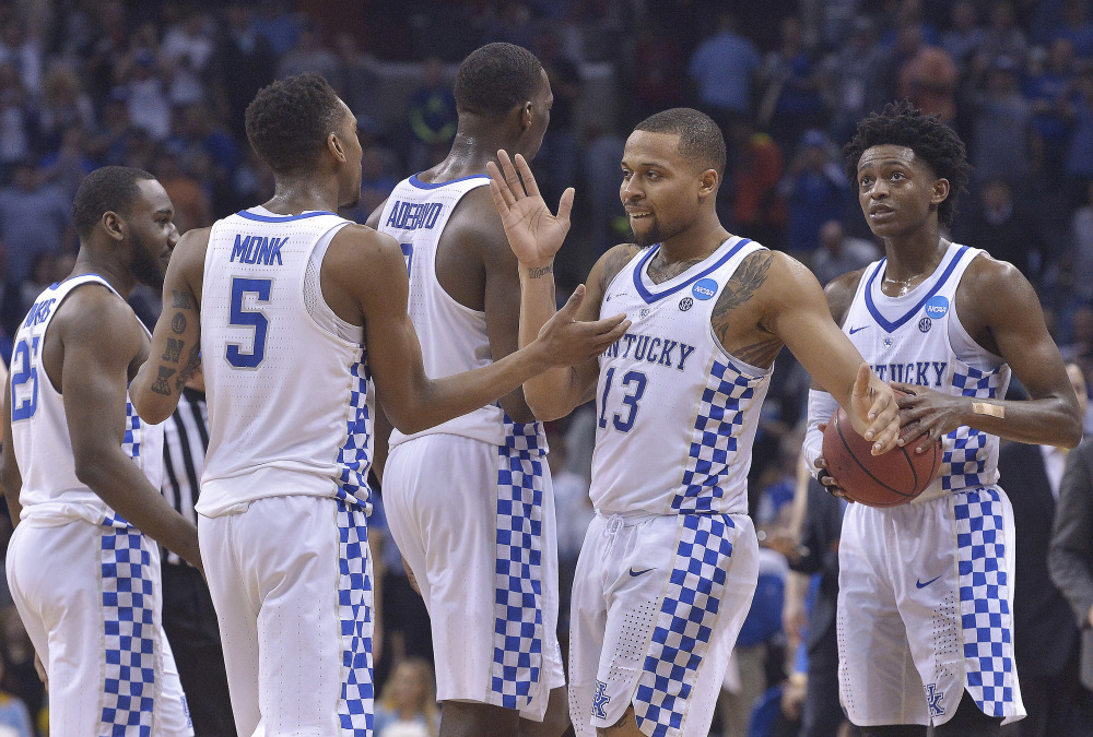 Kentucky players celebrate their 86-75 win over UCLA on Friday night in the South Regional semifinal in Memphis, Tenn.