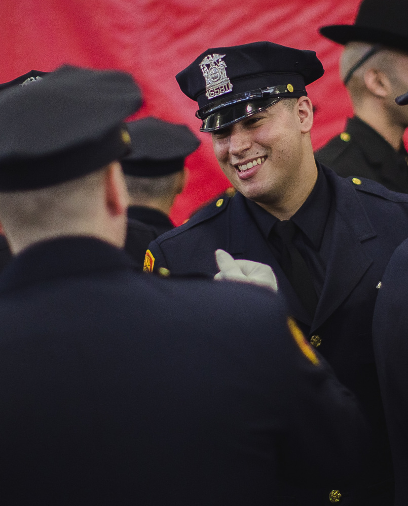 Matias Ferreira celebrates during graduation from the Suffolk County Police Department Academy in Suffolk, N.Y., Friday. Ferreira is a former Marine lance corporal who lost his legs below the knee in Afghanistan in 2011.