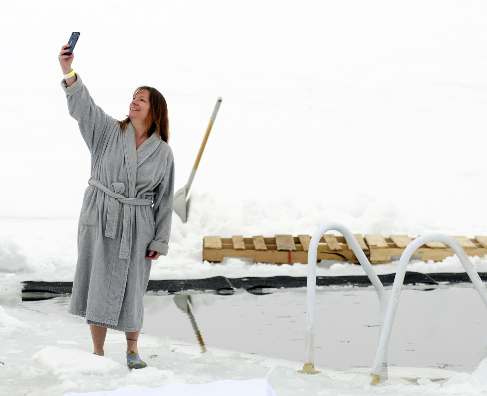 Rhonda Ziehl of Foster, R.I., takes a selfie next to a hole in the Maranacook Lake ice before the Maine Law Enforcement Torch Run Ice Out Plunge on Saturday at Winthrop's town beach.