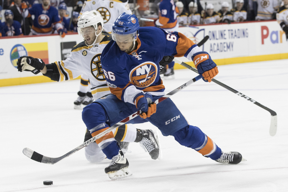 New York Islanders right wing Joshua Ho-Sang controls the puck as he skates against Boston Bruins defenseman Colin Miller during the second period of their game in New York on Saturday night. The Bruins won 2-1. (Associated Press/Mary Altaffer)