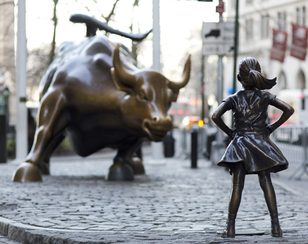 """The """"Charging Bull"""" and """"Fearless Girl"""" statues stand on Lower Broadway in New York. The bull has stood as an image of the spirit of Wall Street."""