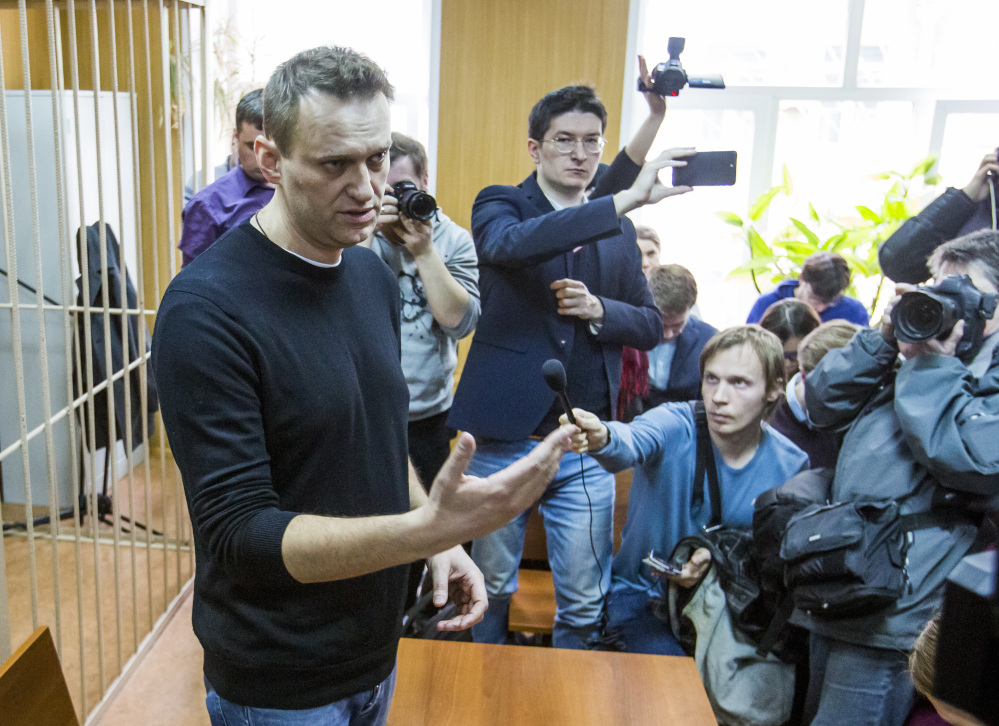 Russian opposition leader Alexei Navalny, foreground, speaks to the press in a courtroom in Moscow on Monday, a day after being arrested while on his way to a major opposition rally. A Moscow court handed a 15-day jail term to Navalny, the protest organizer.