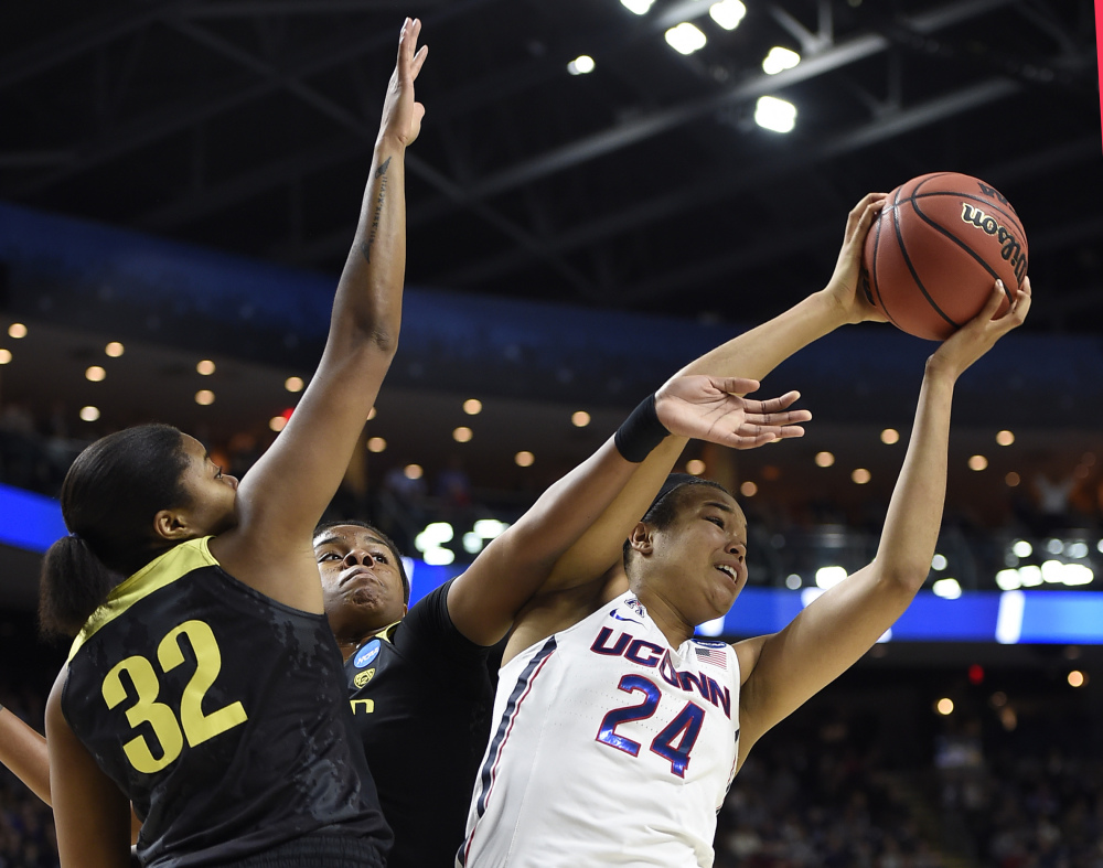 Oregon's Oti Gildon, left, and Ruthy Hebard, center, defend against Connecticut's Napheesa Collier during the first half the Huskies' 90-52 win in a regional final Monday in Bridgeport, Connecticut.