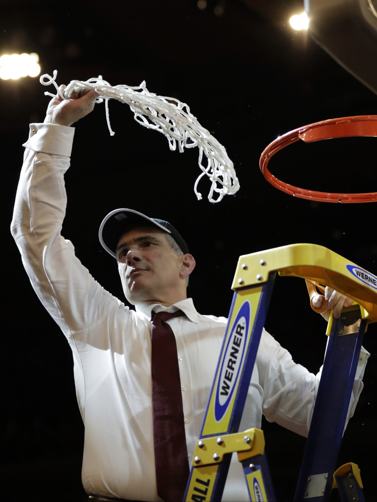 South Carolina head coach Frank Martin swings the net around after cutting it down after beating Florida 77-70 in the East Regional championship game of the NCAA men's college basketball tournament on Sunday.