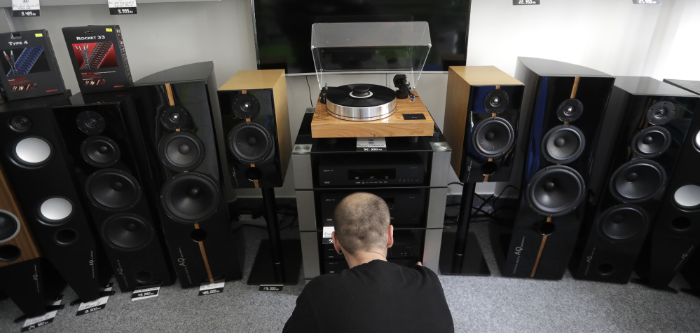 A shop assistant in Prague, Czech Republic, plays a record on a turntable manufactured at the SEV Litovel factory. The firm is the world's largest maker of quality turntables.