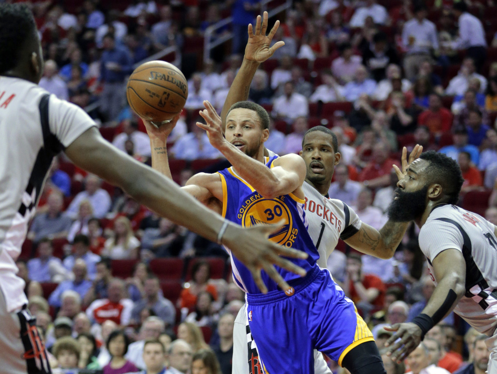 The Warriors' Stephen Curry dishes the ball between Houston Rockets' Clint Capela, Trevor Ariza and James Harden in the first half of Golden State's 113-106 win at Houston. Curry scored 32 points.