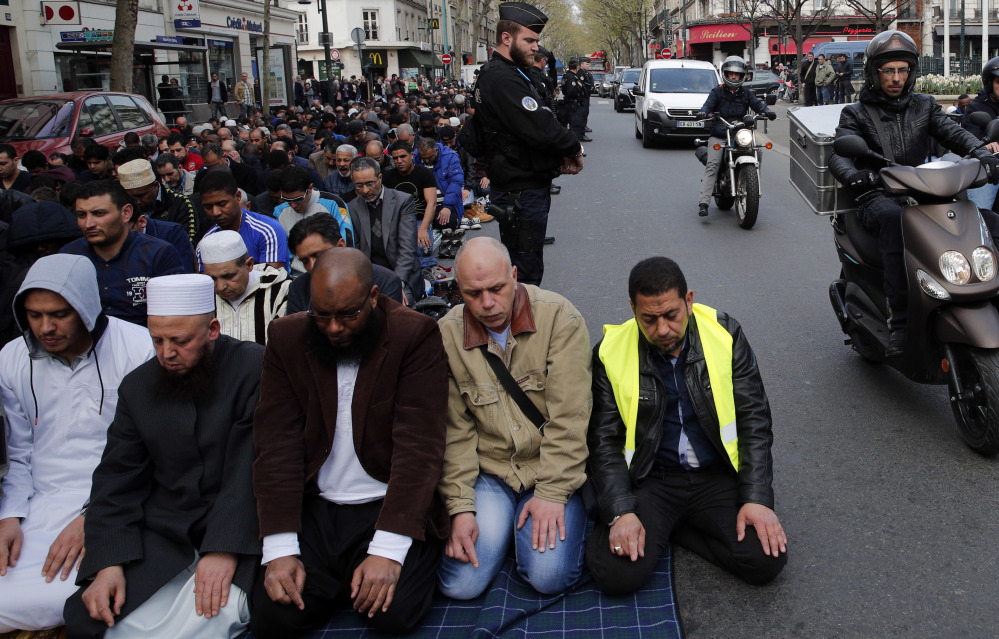 Hundreds of Muslims pray on the street in front of the town hall plaza in the Paris suburb of Clichy la Garenne on Friday.