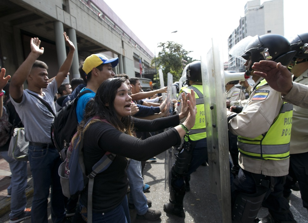 University students clash with Bolivarian National Police Officers during a protest in Caracas, Venezuela on Friday, Venezuelans have been thrust into a new round of political turbulence after the government-stacked Supreme Court gutted their congress of its last vestiges of power, drawing widespread condemnation from foreign governments and sparking protests in the capital.