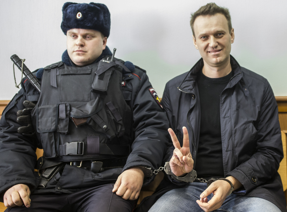 Opposition leader Alexei Navalny handcuffed to a guard in court in Moscow. Navalny is serving 15 days on charges of resisting police.