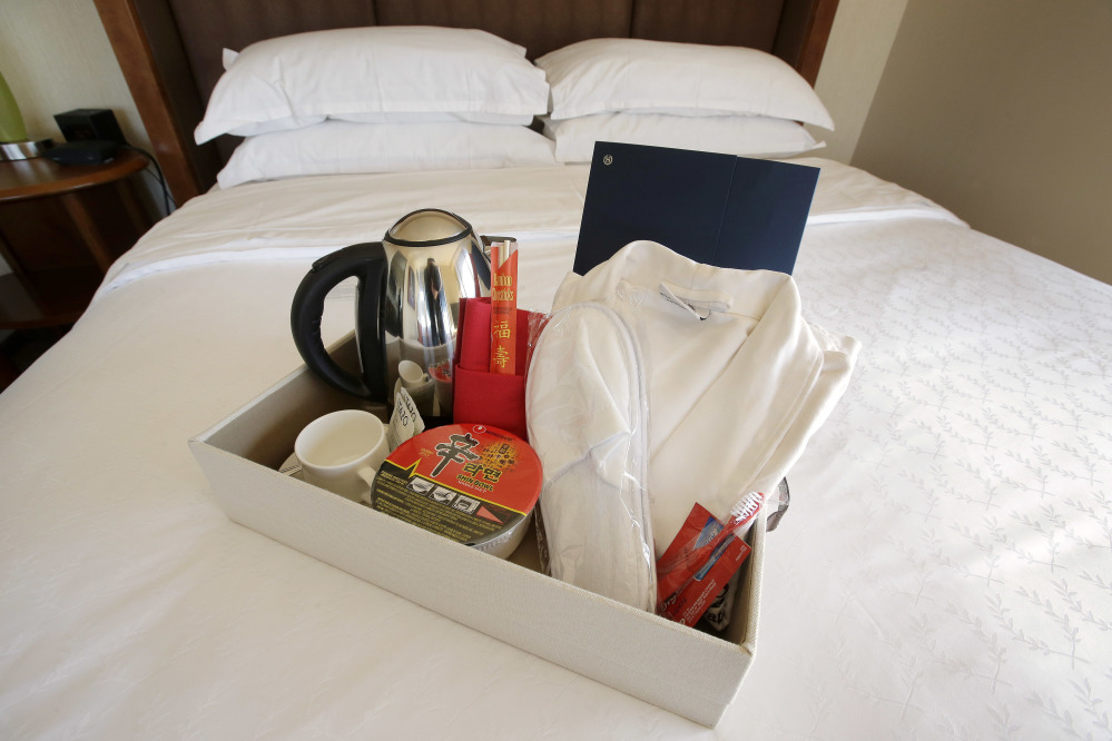 Items in a welcoming kit for Chinese travelers at the Sheraton Boston Hotel include from the left, an electric kettle, green tea, instant noodles, slippers and a robe.