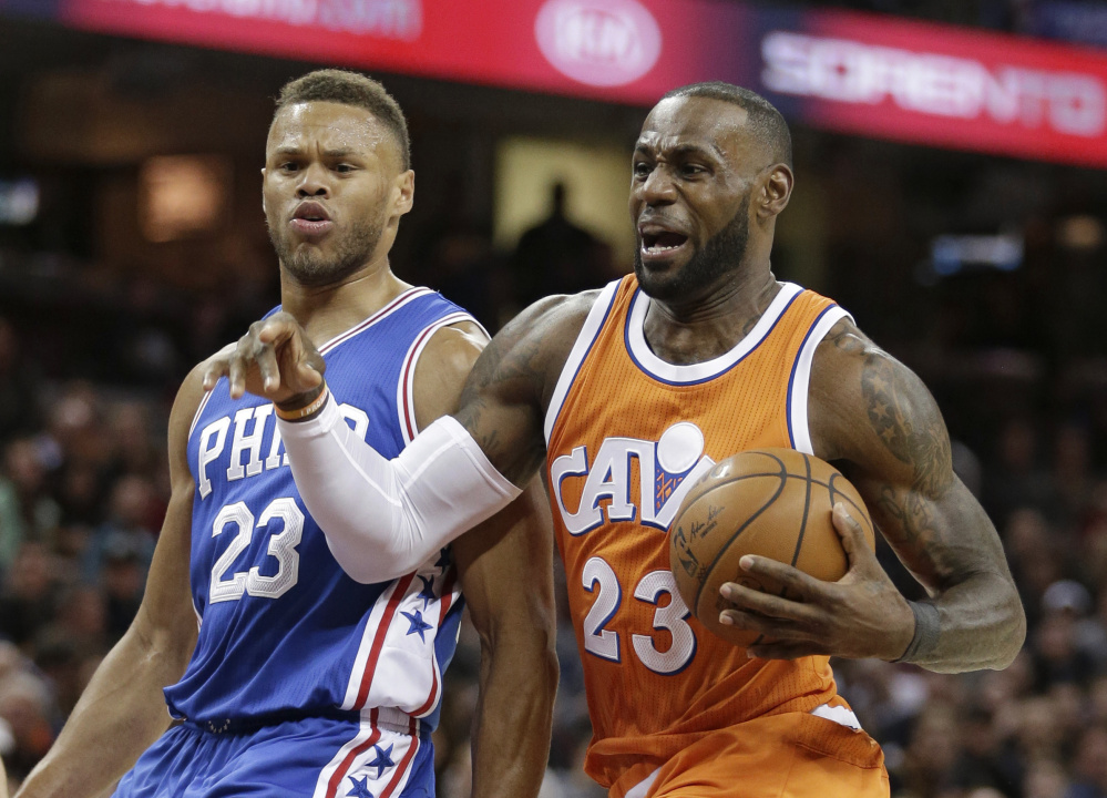 Cleveland's LeBron James, right, drives to the basket against the 76ers' Justin Anderson during the first half of their game in Cleveland on Friday night. The Cavaliers won 122-105 to halt a three-game losing streak.