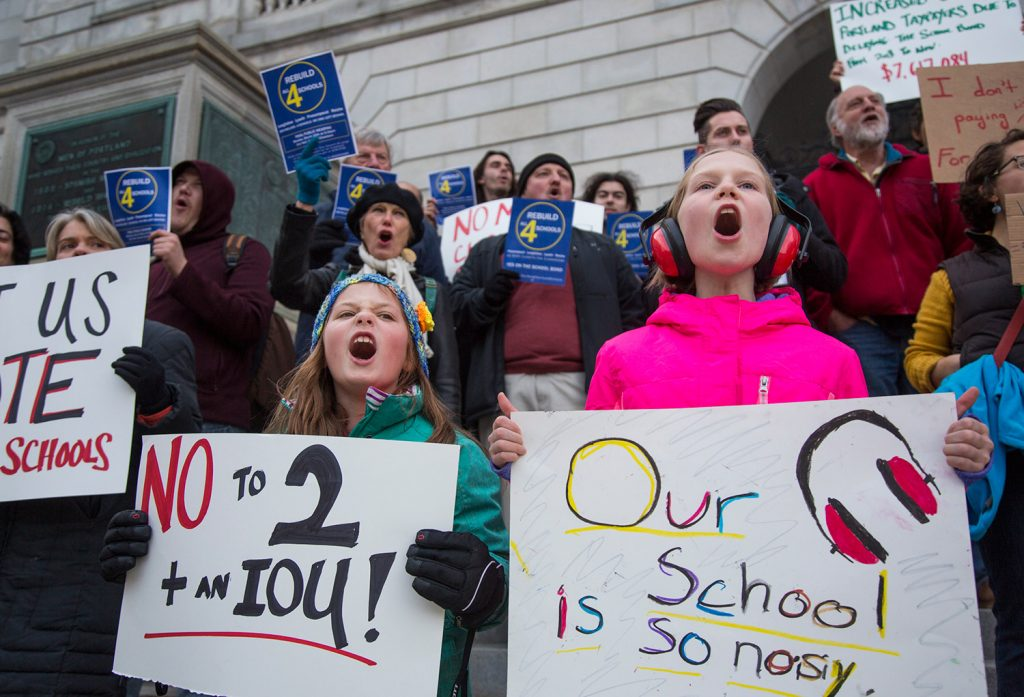 Isabella Figdor, 9, left, and Nina Schafer, 8, students at Reiche Elementary School, join in Tuesday's rally at City Hall.