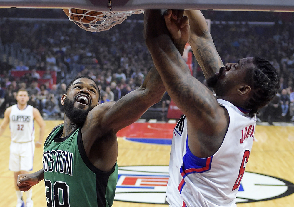 Clippers center DeAndre Jordan, right, dunks as Celtics forward Amir Johnson defends during the first half of Monday, night's game in Los Angeles.