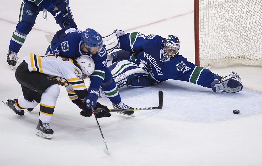 Boston Bruins left wing Brad Marchand scores against Vancouver Canucks goalie Ryan Miller while being checked by Canucks defenseman Alexander Edler during the third period of Monday night's game  in Vancouver.