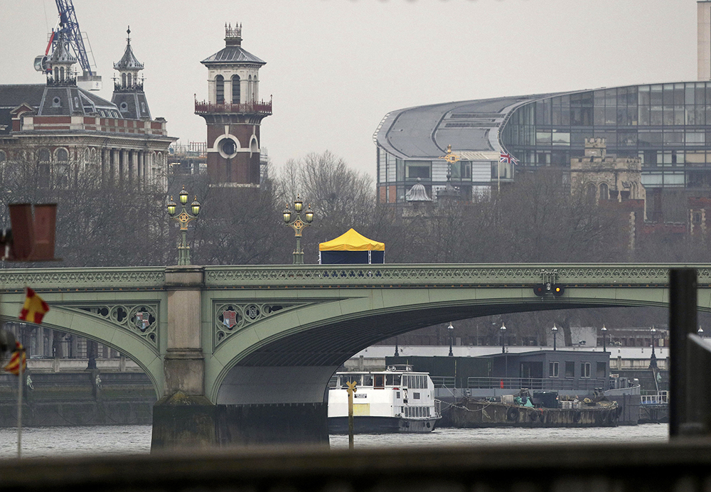 A forensics tent on Westminster Bridge is seen from Victoria Embankment in London on Thursday, a day after an attacker killed three people before being fatally shot by police inside the gates of Parliament.