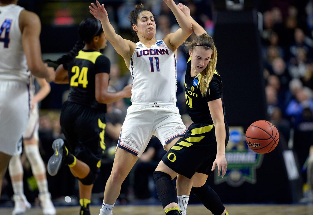 Oregon's Sabrina Ionescu tries to gather the ball after running into the defense of Connecticut's Kia Nurse in the first half of Monday night's regional final in Bridgeport, Conn. Connecticut advanced to the Final Four for the tenth straight year.