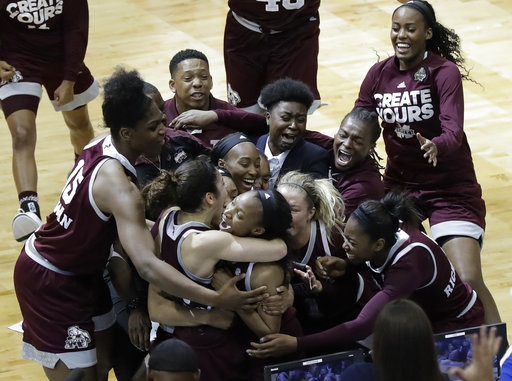 Mississippi State guard Morgan William, center, celebrates with teammates after she hit the winning shot at the buzzer in overtime to defeat Connecticut.