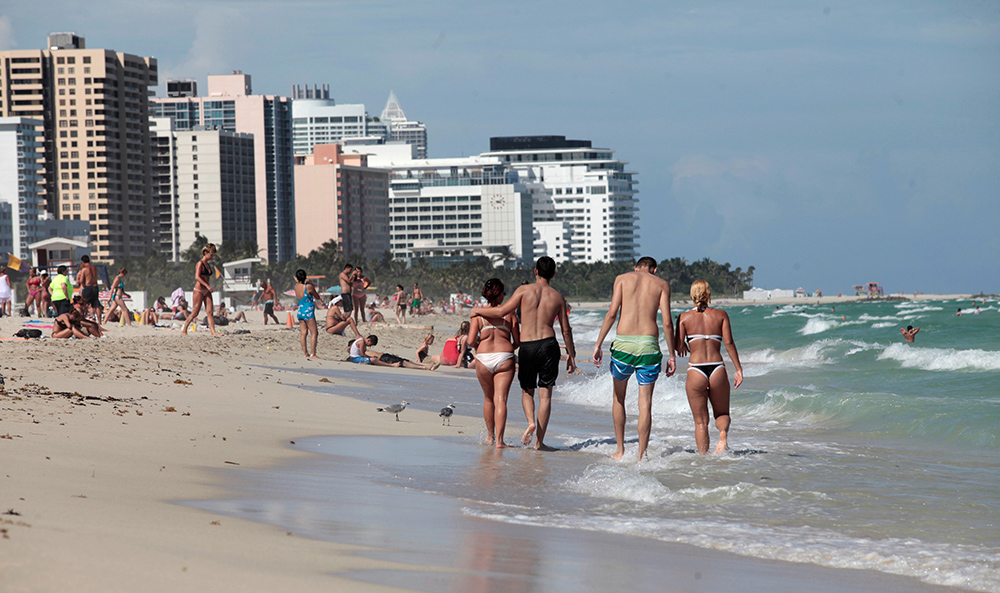 Tourists stroll the beach in Miami on Oct. 5, 2016.  Miami, New York and Los Angeles, being among the most popular destinations for foreign travelers, are especially vulnerable to any tourism declines.