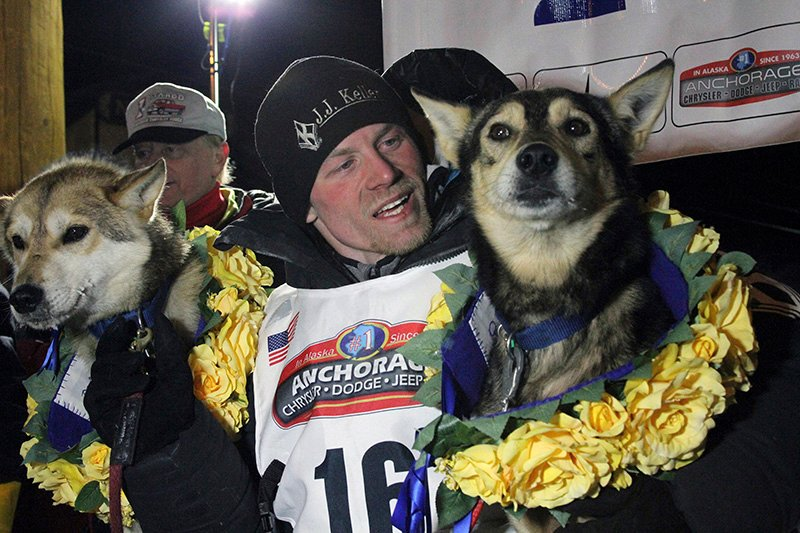 Dallas Seavey in 2016  posing with his lead dogs Reef, left, and Tide after finishing the Iditarod Trail Sled Dog Race in Nome, Alaska.