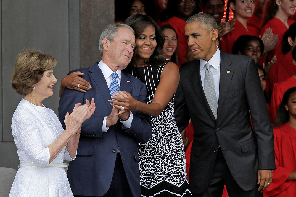 Michelle Obama hugs former President George W. Bush as she arrives with President  Obama and former first lady Laura Bush for the dedication of the Smithsonian's National Museum of African American History and Culture in Washington on Sept. 24, 2016.