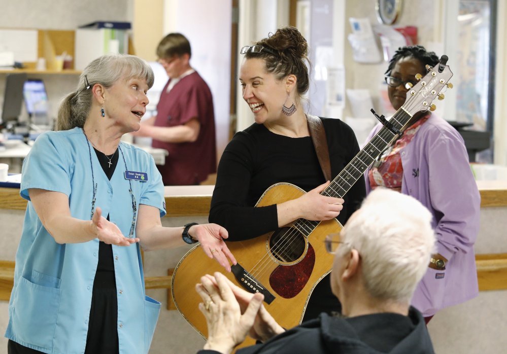 Singer-songwriter Sorcha Cribben-Merrill shares a laugh with nurse Susan Stadnicki and a resident following a recent performance at the memory loss unit at Saint Joseph's Rehabilitation and Residence in Portland. Below, Cribben-Merrill and Stadnicki entertain a patient during her visit.