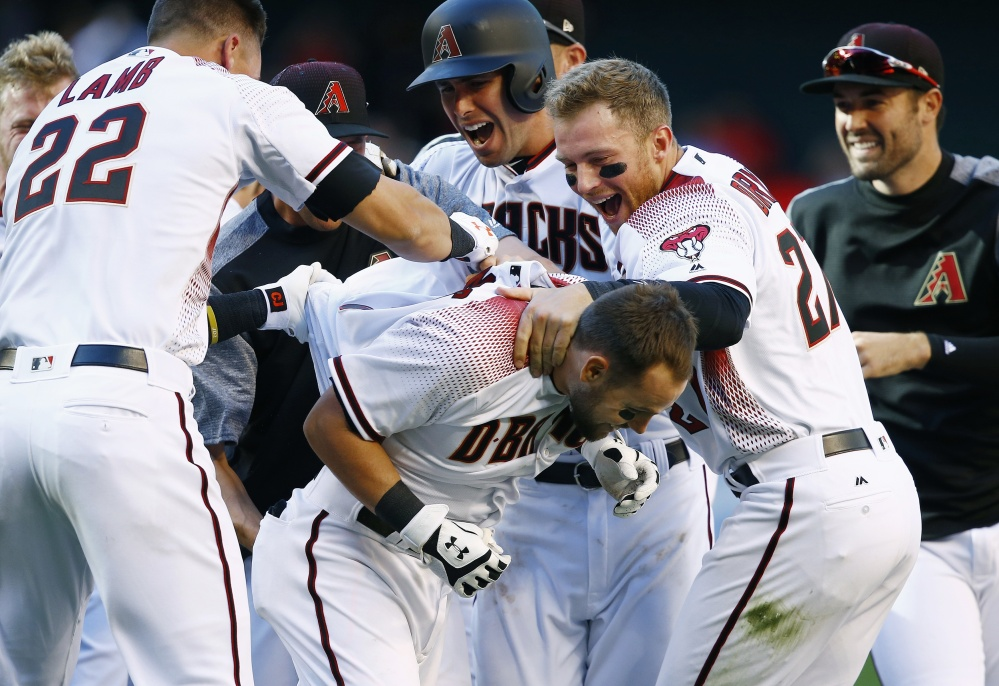 Arizona's Chris Owings, front, celebrates his walk-off single with Jake Lamb, left, Paul Goldschmidt, second from left, Brandon Drury, second from right, and Robbie Ray after the Diamondbacks' 6-5 win over San Francisco in a season opener Sunday in Phoenix.