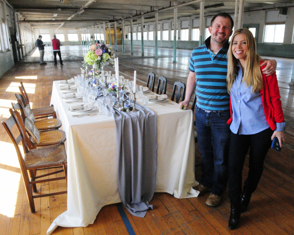 John Butterfield of Leaf and Petal's Flower Design and venue co-owner Veronica Carbona stand beside a table they decorated Thursday at Penthouse V on the fifth floor of the Winthrop Commerce Center, formerly the Carleton Woolen Mill.