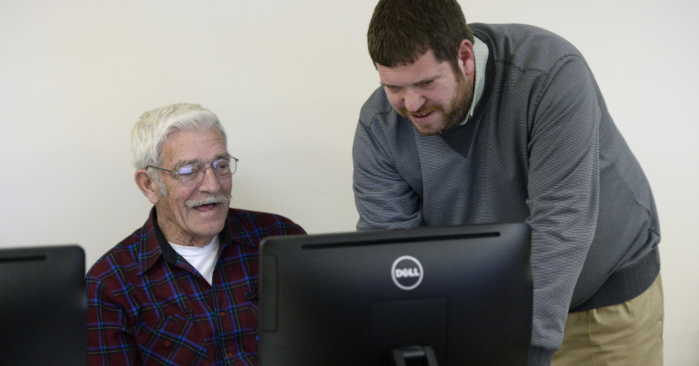 Michael Lamoureux works with Bill Kiley, 80, during a technology class in Gray. Kiley owns a computer but didn't know how to navigate it before taking the course.