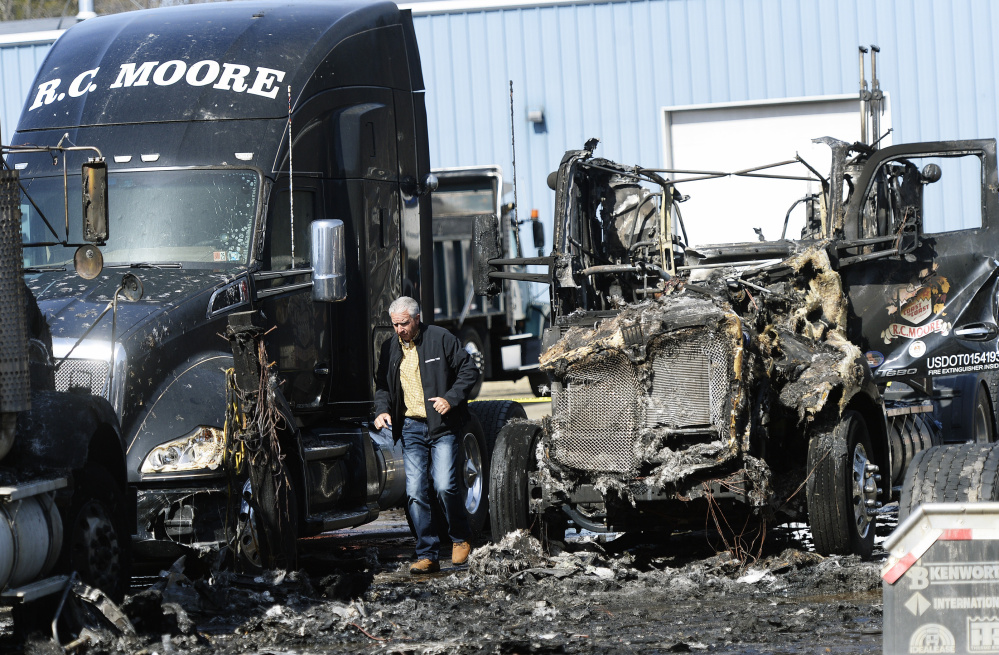Kelly Moore of R.C. Moore looks over the damage to trucks Monday at the company's depot in Poland. The State Fire Marshal's Office is investigating the coordinated arson fires Sunday night that destroyed six tractor-trailer cabs and damaged two others at the company's facilities in Poland and Scarborough. (Staff photo by Shawn Patrick Ouellette/Staff Photographer)