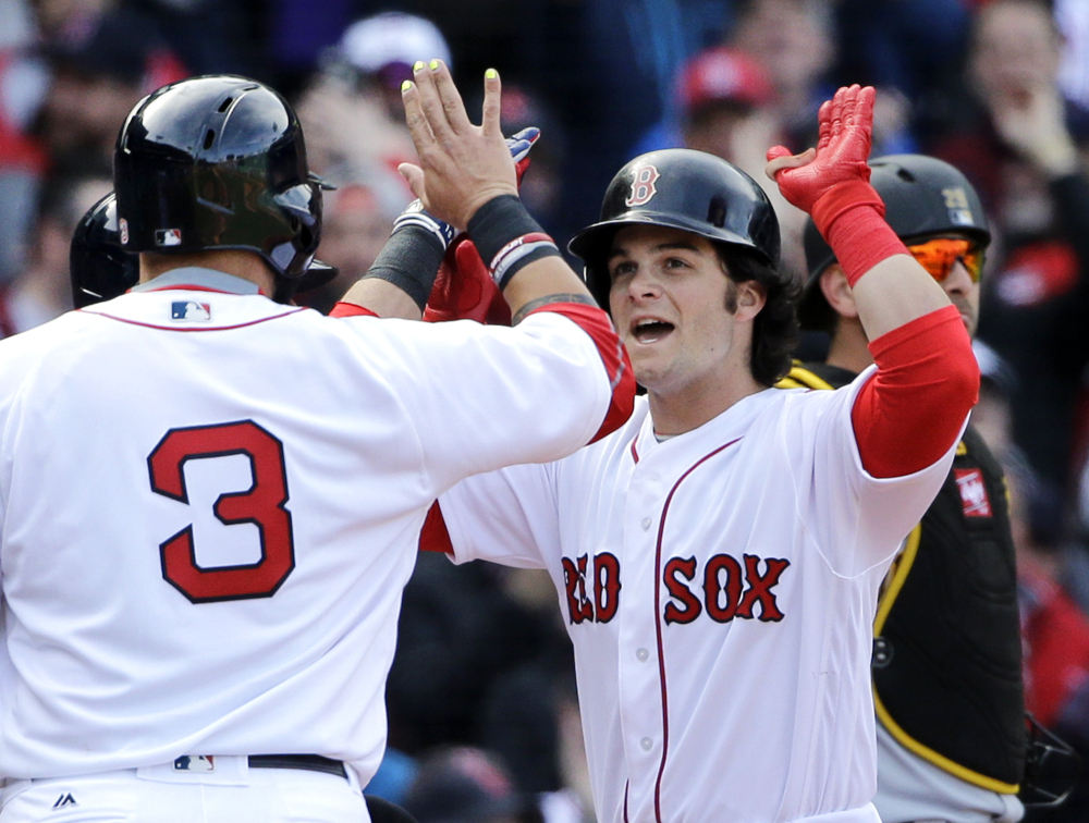Andrew Benintendi celebrates his three-run homer with Red Sox teammate Sandy Leon in the fifth inning Monday against the Pittsburgh Pirates at Fenway Park. The homer capped a five-run inning, and the Red Sox held on for a 5-3 win in their season opener. (Associated Press/Elise Amendola)