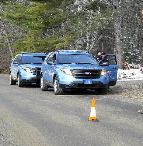 Two Maine State Police troopers consult with each other outside a residence on Winnecook Road in Burnham while investigating the death of Joyce Wood on Sunday. A pair of boots lie in the road in the foreground.