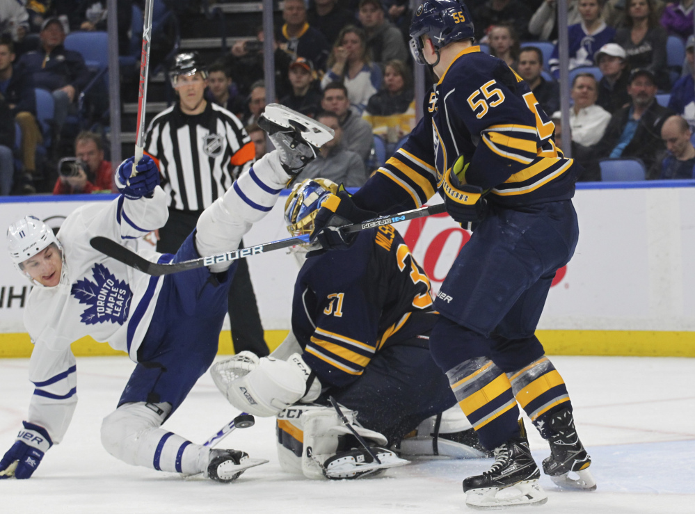 Buffalo defenseman Rasmus Ristolainen, right, knocks down Toronto forward Zach Hyman during the second period of a 4-2 win Monday by the Maple Leafs at Buffalo, N.Y.