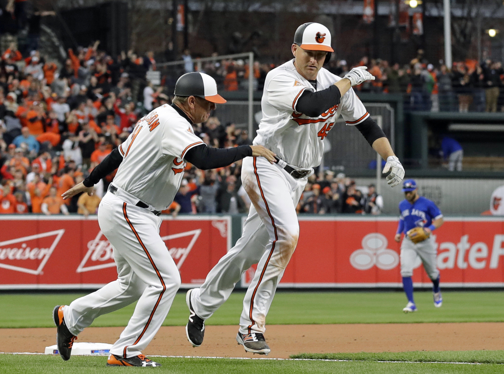 Baltimore third-base coach Bobby Dickerson, left, celebrates with Mark Trumbo as he rounds third base after his solo homer in the 11th inning the Orioles' 3-2 win over Toronto on Monday.