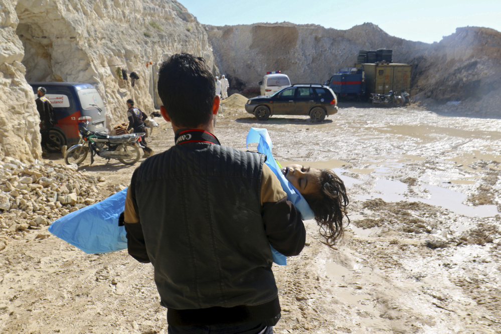 A man carries the body of a dead child Tuesday after what rescue workers described as a suspected gas attack in the town of Khan Sheikhoun in rebel-held Idlib, Syria.
