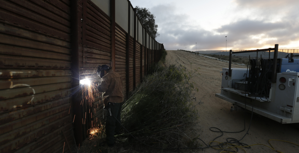 A U.S. Border Patrol agent welds a section of steel over a hole cut in the existing border wall in San Diego in 2013. Bids on the first design contracts for a full wall, due Tuesday, show companies are preparing for the worst if they get the potentially lucrative but controversial job.