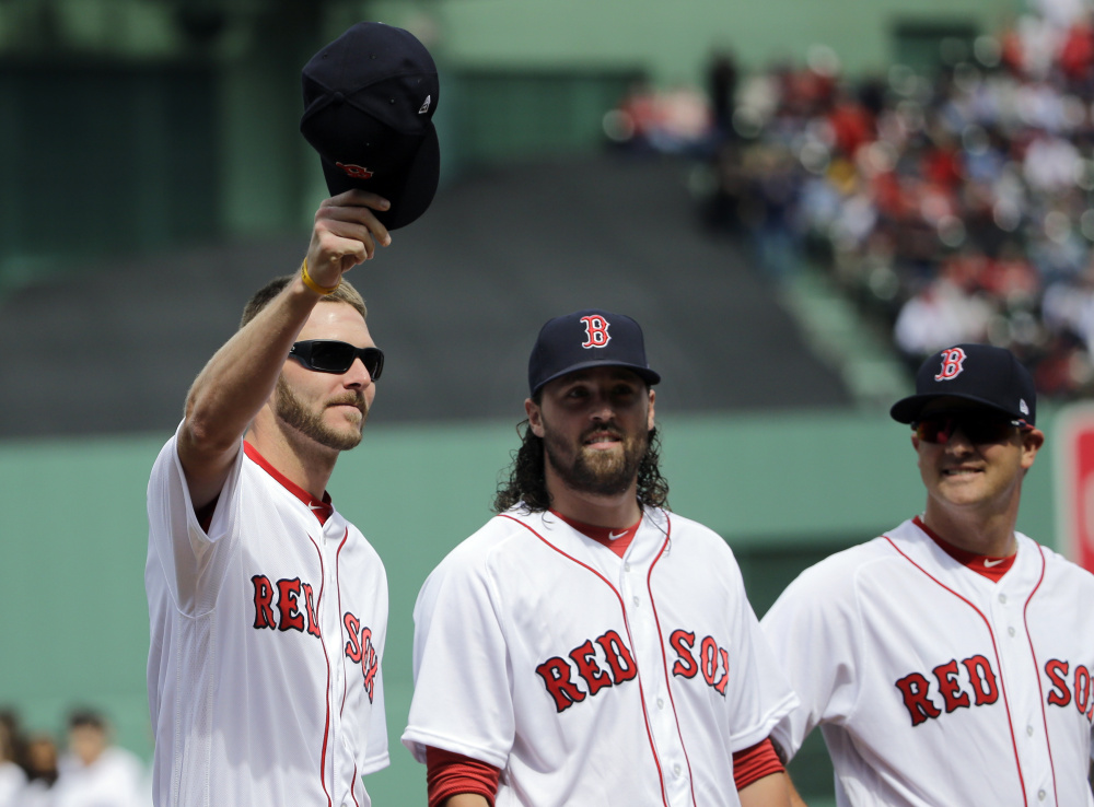 Boston Red Sox pitcher Chris Sale lifts his cap to cheering fans during Red Sox Home Opening Day ceremonies at Fenway Park on Monday.