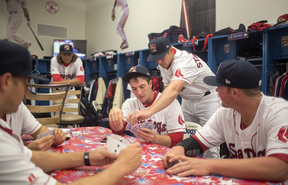There are many ways to pass the time in the clubhouse as Teddy Stankiewicz leans over and helps Jordan Procyshen play his hand in a card game in the Sea Dog's clubhouse at Hadlock Field on Tuesday.