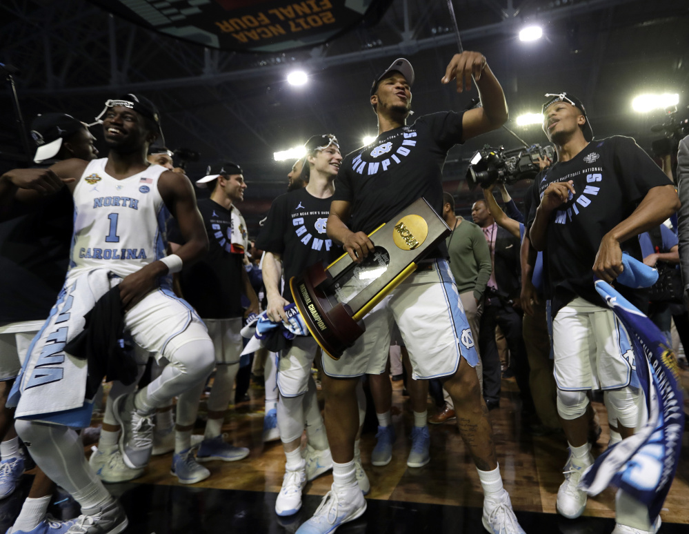 North Carolina's Kennedy Meeks holds the championship trophy as he celebrates with his teammates after defeating Gonzaga 71-65 in the NCAA men's basketball final Monday.