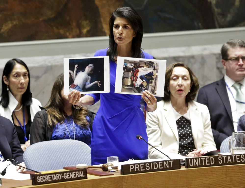 Nikki Haley, the U.S. ambassador to the United Nations, shows pictures of Syrian victims of Tuesday's chemical attack as she addresses a meeting of the Security Council on Wednesday. The council met in an emergency session to consider a resolution to back an investigation and compel the Syrian government to cooperate.