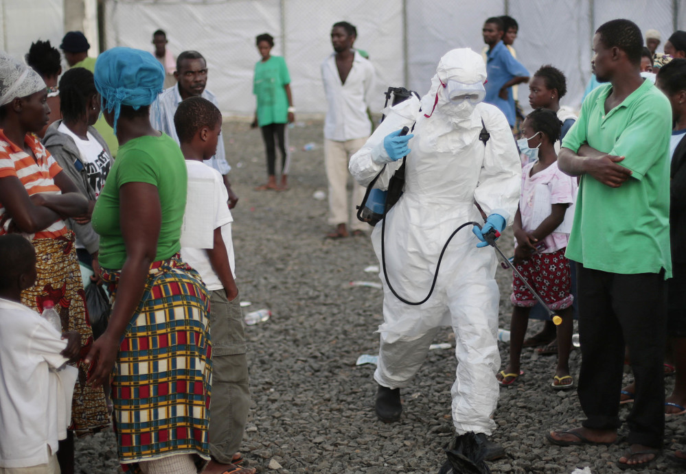 A medical worker sprays people at an Ebola treatment center in Liberia in 2014. A once busy treatment unit in Paynesville, Liberia, was decommissioned Wednesday.