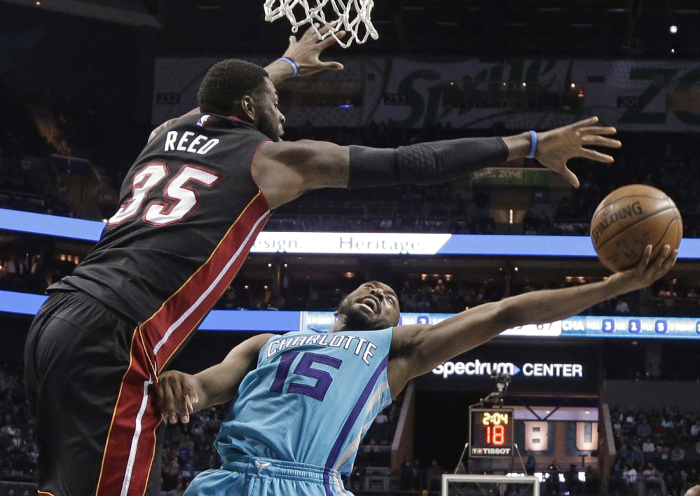 Kemba Walker of the Charlotte Hornets attempts to get a shot over Willie Reed of the Miami Heat during the second half of Miami's 112-99 victory Wednesday night. The Heat are tied for eighth in the East.