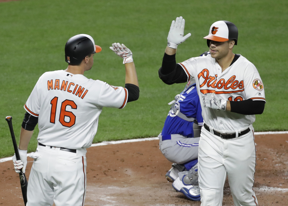 Baltimore's Chris Davis, right, high-fives teammate Trey Mancini after hitting a solo home run during the fourth inning of the Orioles' 3-1 win at home against Toronto on Wednesday night.