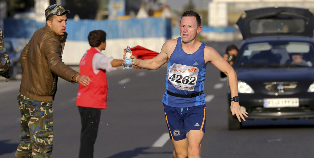 "An Iranian soldier hands a bottle of water to a British runner during the ""Persian Run"" in Tehran, Iran, on Friday."